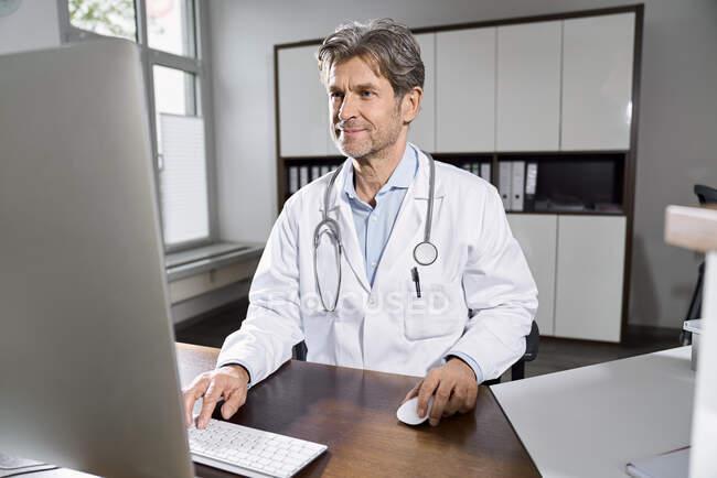 Medico che utilizza il computer alla scrivania nel suo studio medico — Foto stock