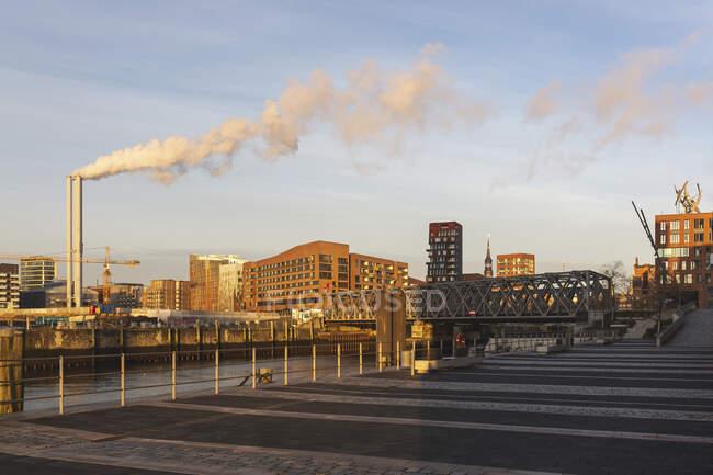 Alemania, Hamburgo, HafenCity puerto al amanecer con humo saliendo de chimeneas industriales en el fondo - foto de stock