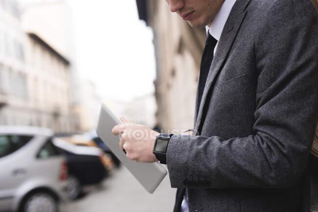 Вигляд молодого бізнесмена з цифровою табличкою, що дивиться на розумник. — стокове фото