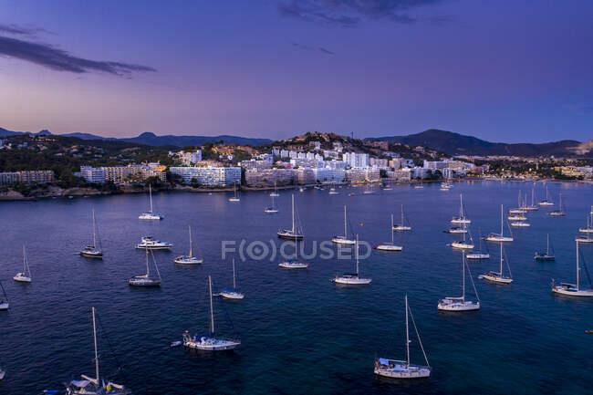 Spagna, Maiorca, Santa Ponsa, Barche galleggianti in acque costiere al tramonto con la città sullo sfondo — Foto stock
