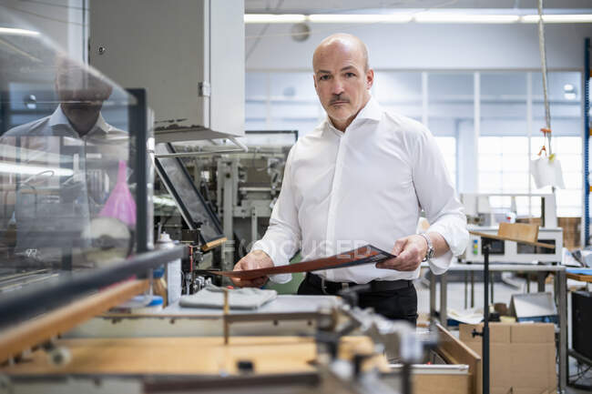 Businessman in a printing plant checking product — Stock Photo