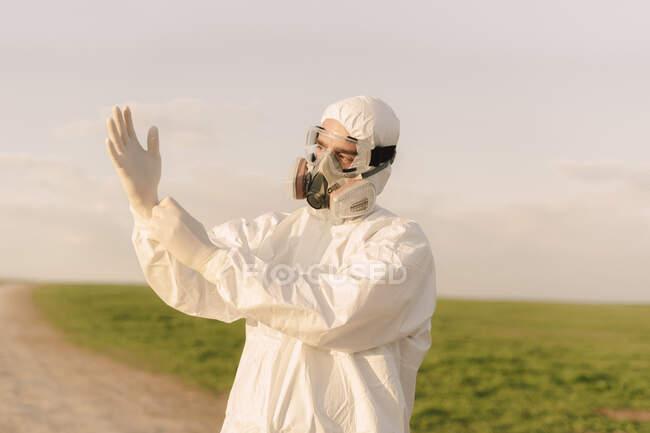 Hombre con traje protector y máscara en el campo poniéndose guantes protectores - foto de stock