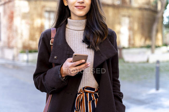 Close-up of woman holding smartphone in the city — Stock Photo