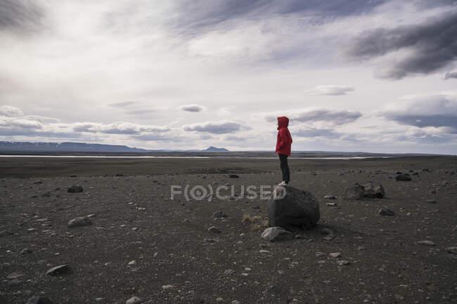 Молода жінка стоїть на скелі в вулканічному нагір