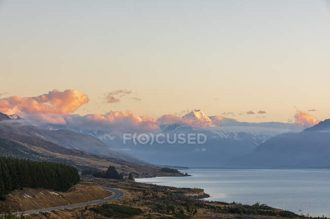 New Zealand, Scenic view of New Zealand State Highway 80 stretching along shore of Lake Pukaki at dawn with Mount Cook in background — Stock Photo