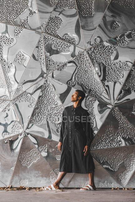 Молодий чоловік у чорному кафтані стоїть біля стіни. — стокове фото