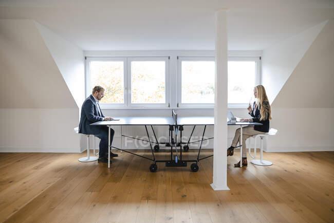 Homme d'affaires et femme d'affaires travaillant à la table de ping-pong au bureau — Photo de stock