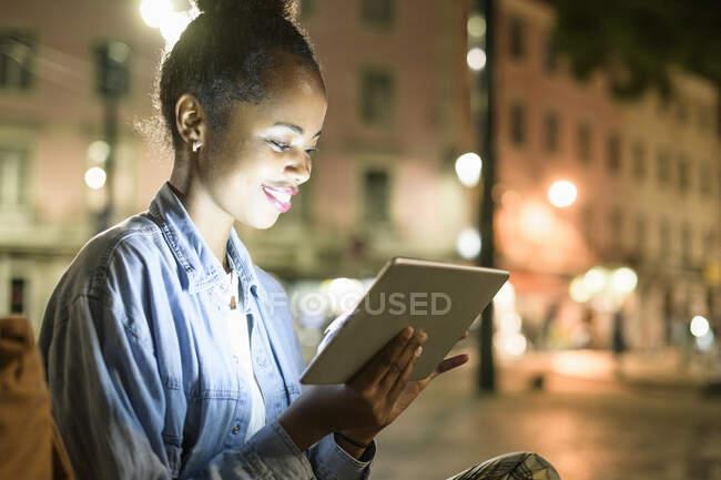 Jovem sorridente usando tablet digital na cidade à noite, Lisboa, Portugal — Fotografia de Stock