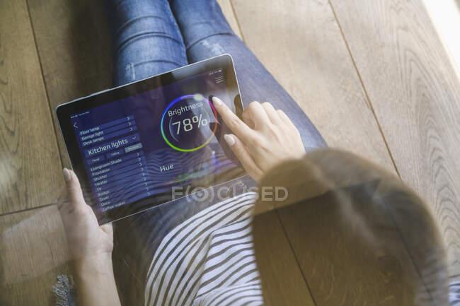 Mujer joven con tableta con funciones de control del hogar inteligente - foto de stock