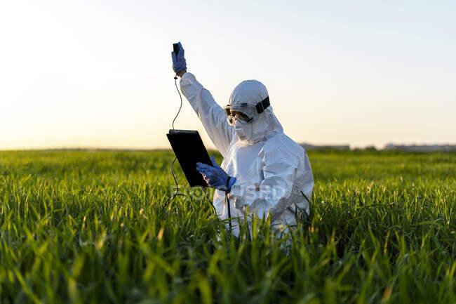Científica investigando en el campo y utilizando un dispositivo de medición - foto de stock