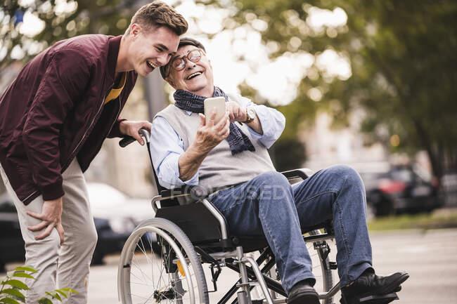 Сміється старша людина в інвалідному візку і його дорослий онук, дивлячись разом на смартфон, розважається. — стокове фото