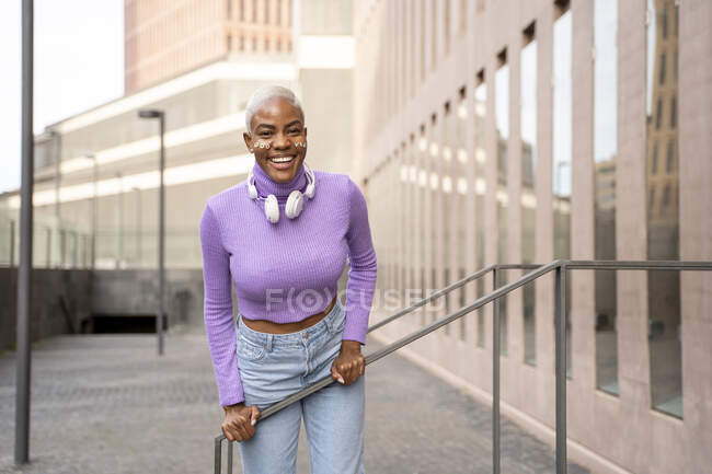 Portrait of white haired woman with white headphones and stickers in her face, good vibes — Stock Photo