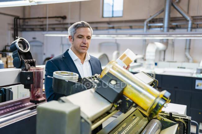 Бізнесмен на фабриці, що дивиться на машину — стокове фото