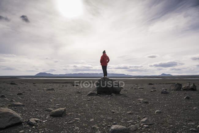 Зрілий чоловік стоїть на скелі в вулканічному нагір