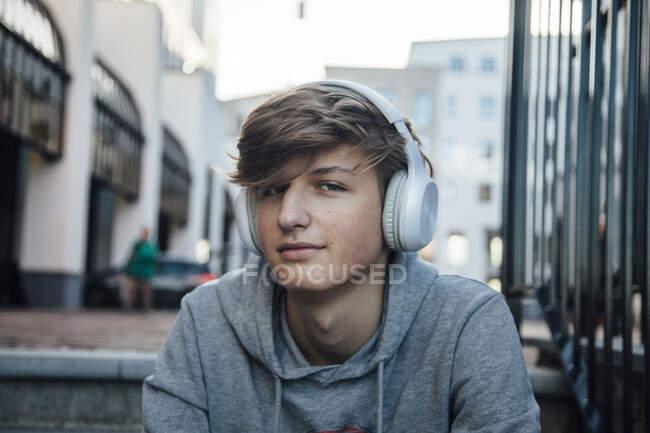Retrato de adolescente con auriculares, sentado en los escalones de la ciudad - foto de stock