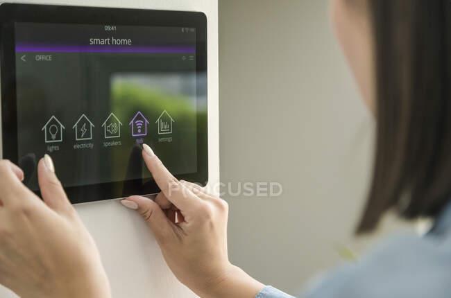Молодая женщина с планшетом с умными функциями домашнего контроля — стоковое фото