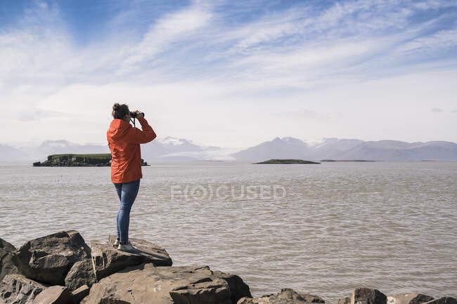 Молода жінка копає валуни, дивлячись через бінокль (Південно - Східна Ісландія). — стокове фото
