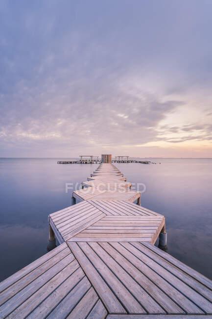 España, Murcia, Santiago de la Ribera, Muelle de madera en mar tranquilo al atardecer - foto de stock