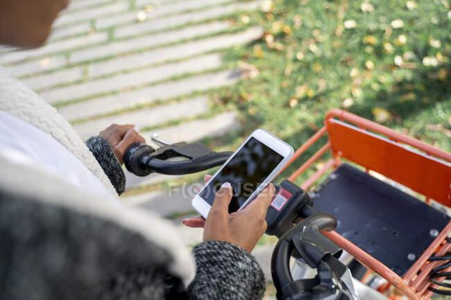 Зайнята жінка за допомогою системи спільного користування велосипедами, утомлює смартфон — стокове фото