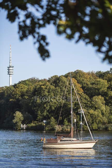 Германия, Бранденбург, Потсдам, Парусник пришвартованы на реке Гавел с телевизионной башней на заднем плане — стоковое фото