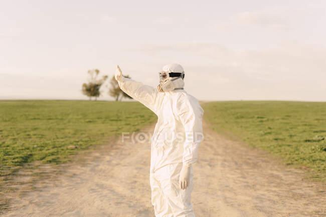 Hombre con traje protector y máscara de pie en la pista de tierra en el campo - foto de stock