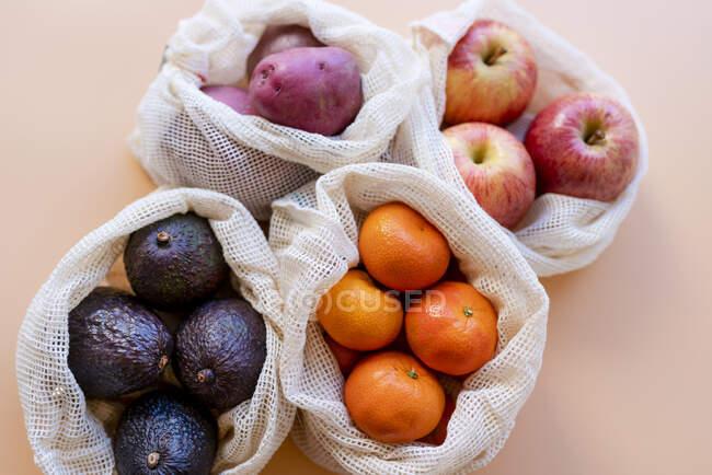 Bolsas de malla reutilizables ecológicas con frutas y verduras frescas - foto de stock