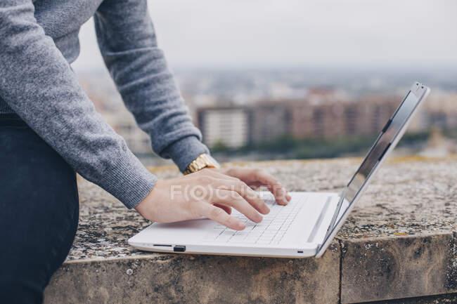 Primer plano de las manos de un joven escribiendo en su portátil en Lleida - foto de stock