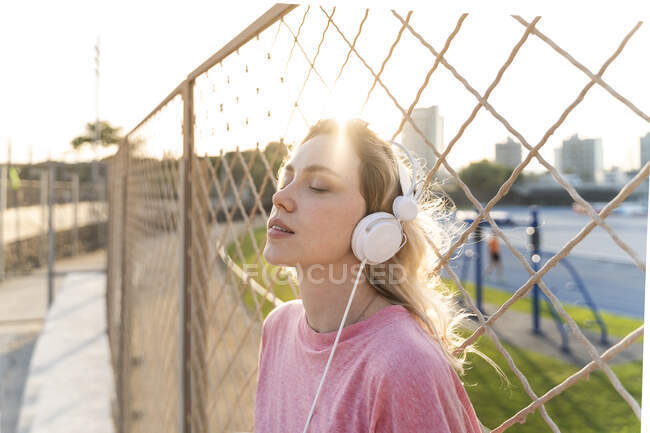 Young woman listening to music at a wire mesh fence — Stock Photo