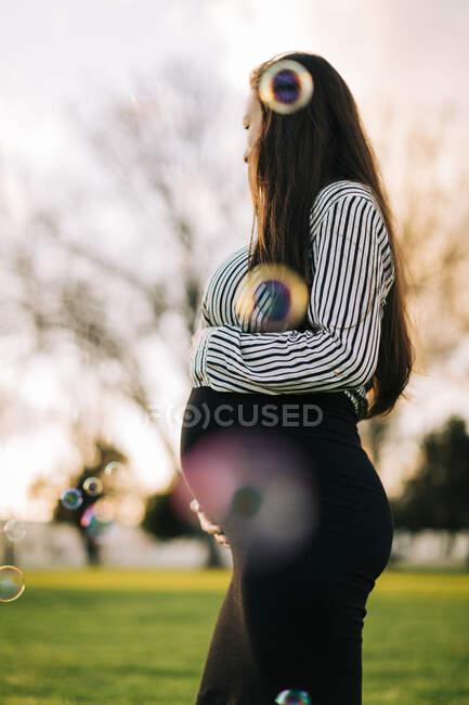 Беременная молодая женщина, окруженная мыльными пузырями в парке на закате — стоковое фото