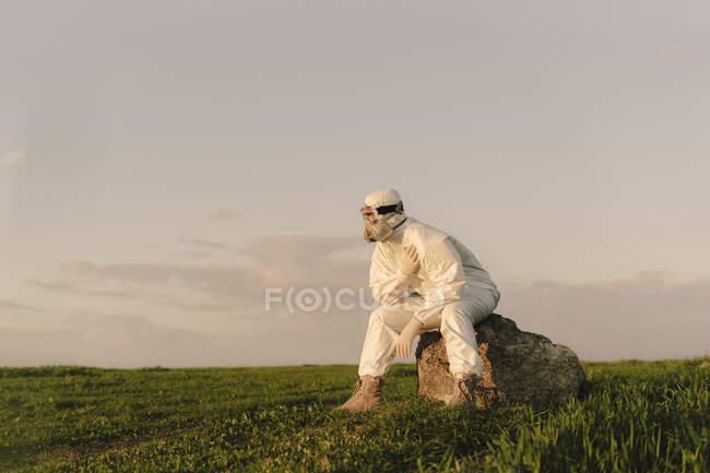 Hombre con traje protector y máscara sentado en una roca en el campo - foto de stock