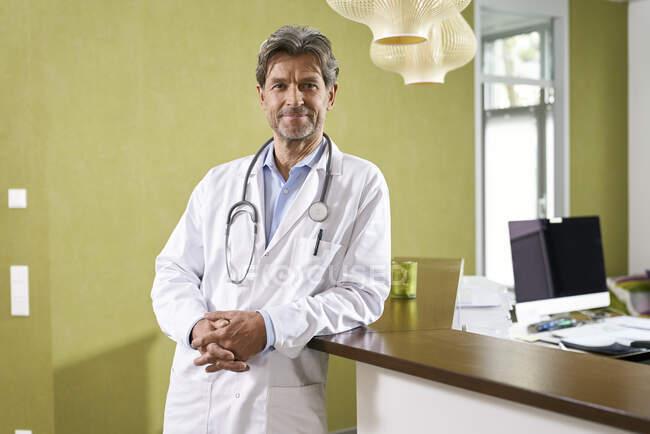 Ritratto di medico fiducioso alla reception nel suo studio medico — Foto stock