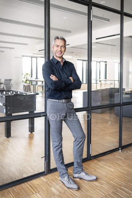 Empresario apoyado en pared de cristal en su oficina, con los brazos cruzados - foto de stock