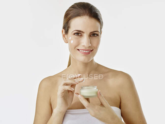 Portrait of smiling woman with cream jar — Stock Photo
