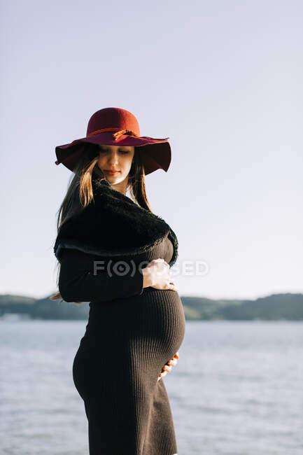 Модная беременная молодая женщина стоит на набережной — стоковое фото