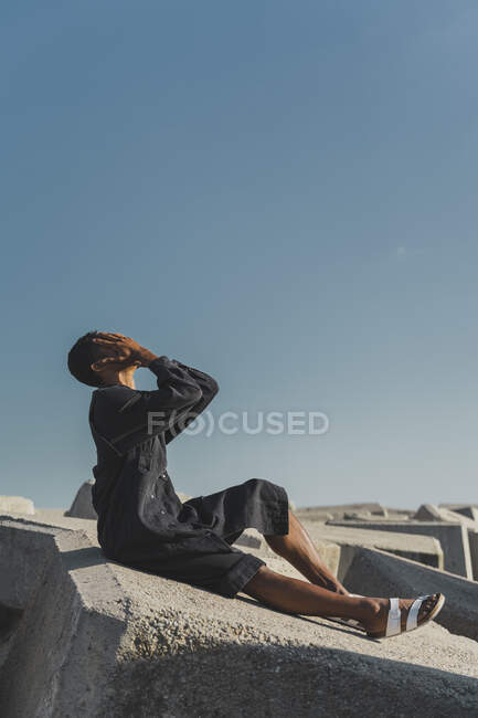 Jovem vestindo kaftan preto sentado em blocos de concreto sob o céu azul cobrindo seu rosto — Fotografia de Stock