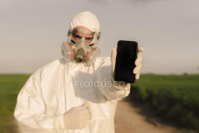 Hombre con traje de protección y máscara en el campo sosteniendo el teléfono celular - foto de stock