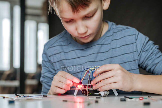 Boy assembling robot at home — Stock Photo