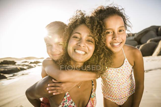 Ritratto di una madre felice con i suoi due figli che si divertono sulla spiaggia — Foto stock