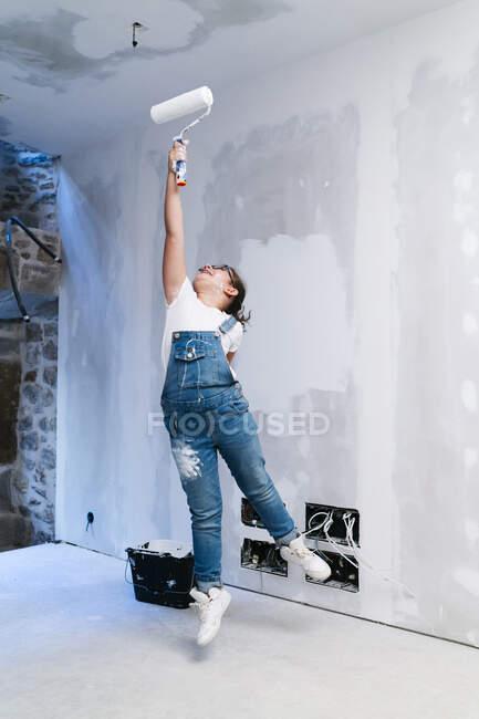 Дівчинка стрибає, малюючи стіну в домі. — стокове фото