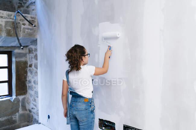 Дівчинка фарбує стіну в будинку. — стокове фото