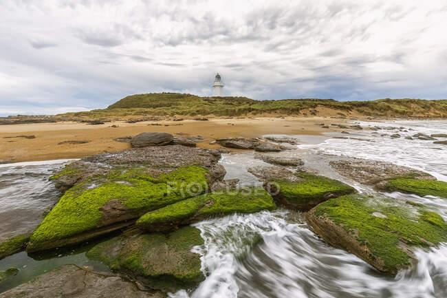 Nueva Zelanda, Oceanía, South Island, Southland, Otara, Rocky Creek y Waipapa Point Lighthouse a lo lejos - foto de stock