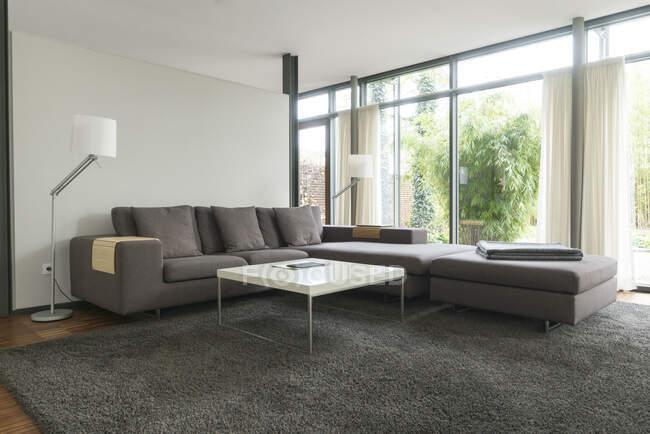 Современная гостиная в дизайнерском доме с большими окнами — стоковое фото