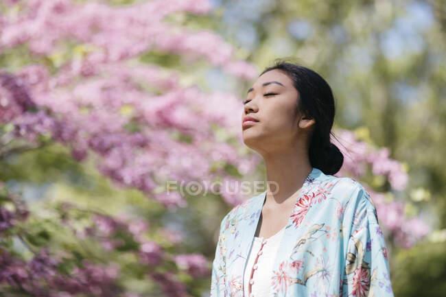 Hermosa mujer joven con cerezo en flor en un jardín público en primavera - foto de stock