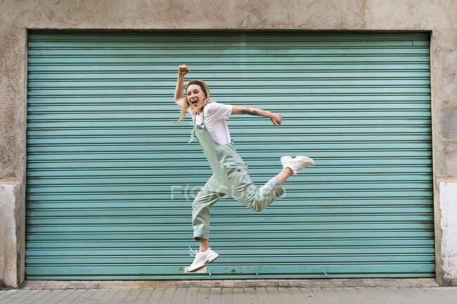 Щаслива молода жінка стрибає з радощів у місті. — стокове фото