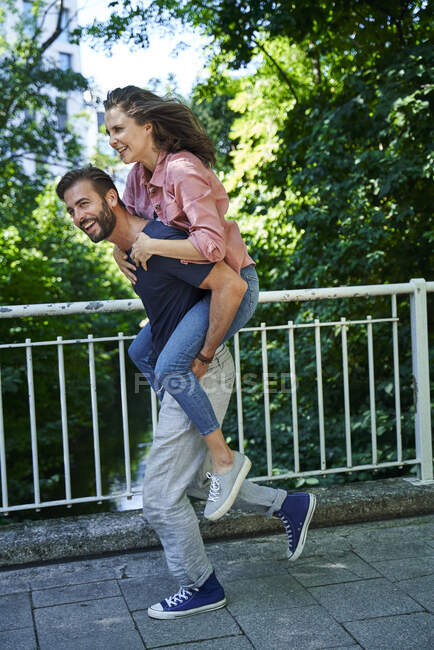 Happy man running and carrying woman piggyback — Stock Photo