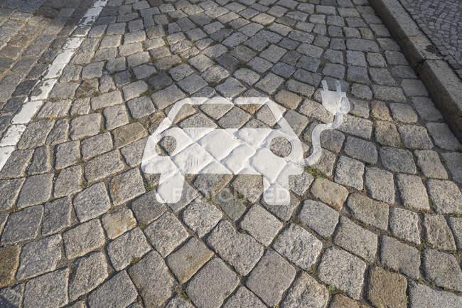 Німеччина, Саксонія-Ангальт, Кедлінбург, Електромобіль заряджає станцію символ на бруківці — стокове фото
