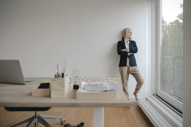 Young businesswoman in office looking out of window — Stock Photo
