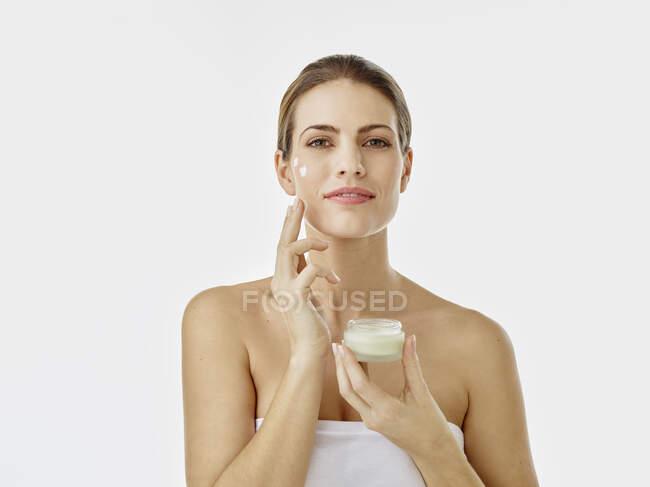 Retrato de mujer sonriente con olla crema aplicando crema hidratante en su cara - foto de stock