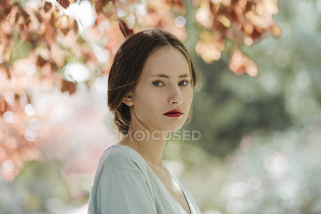Portrait of young woman with red lips in nature — Stock Photo