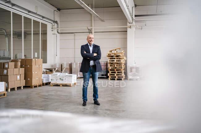 Homme d'affaires debout dans une usine — Photo de stock